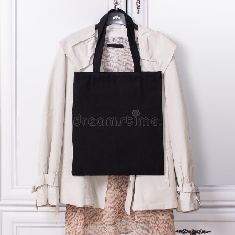 Sac d'emballage noir d'eco de coton sur un cintre avec les vêtements élégants, maquette de conception Paniers faits main photos stock