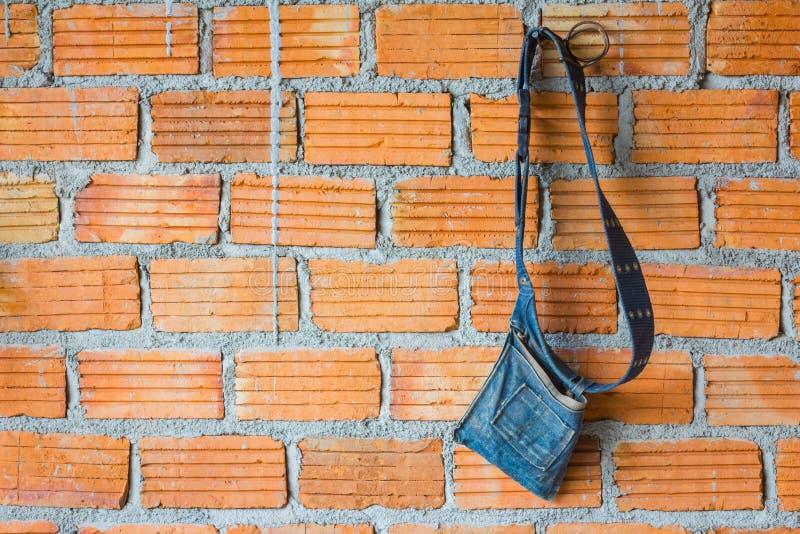 Sac d'outillage de denim sur le mur de briques avec le copyspace du côté gauche photos stock