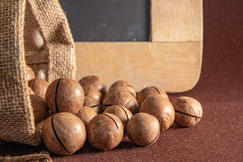 Sac de sac avec la macadamia sur le fond brun image stock