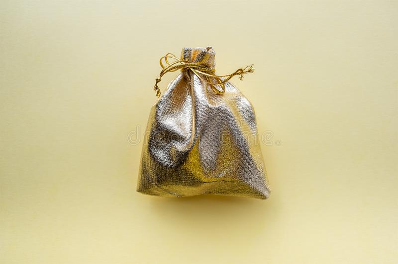 Sac de cadeau de tissu d'or sur un fond jaune Le concept des vacances photos stock