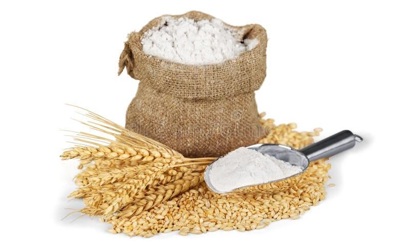 Sac de farine avec du blé et le scoop d'isolement dessus photos stock