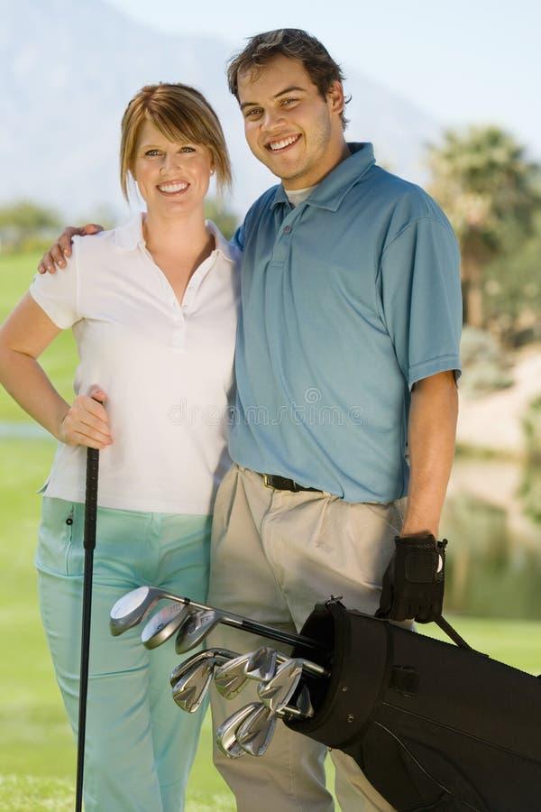 Sac de golf de transport de couples heureux photo stock