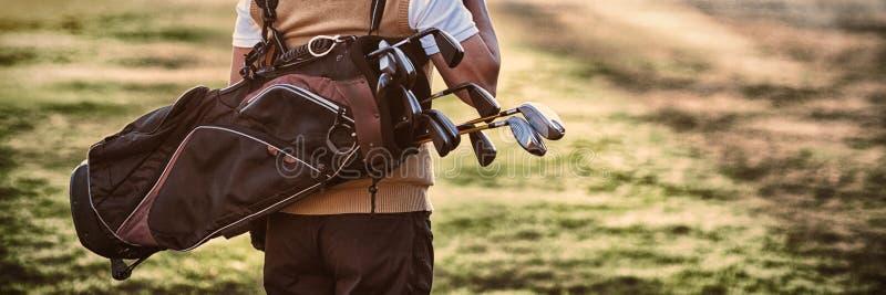 Sac de golf de transport d'homme tout en se tenant sur le champ photos libres de droits