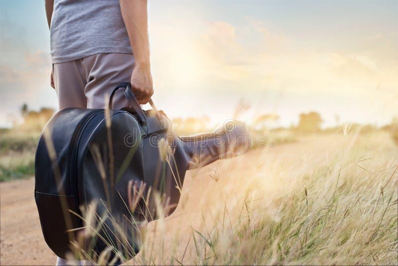 Sac de guitare à disposition sur la route de campagne à l'arrière-plan de nature image stock