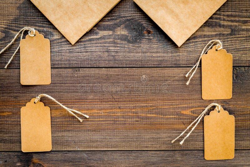 Sac de papier de Brown emballage pour faire des emplettes près des prix à payer sur l'espace en bois de copie de maquette de vue  images stock