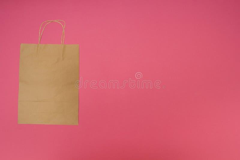 Sac de papier jetable sur le fond rose images libres de droits