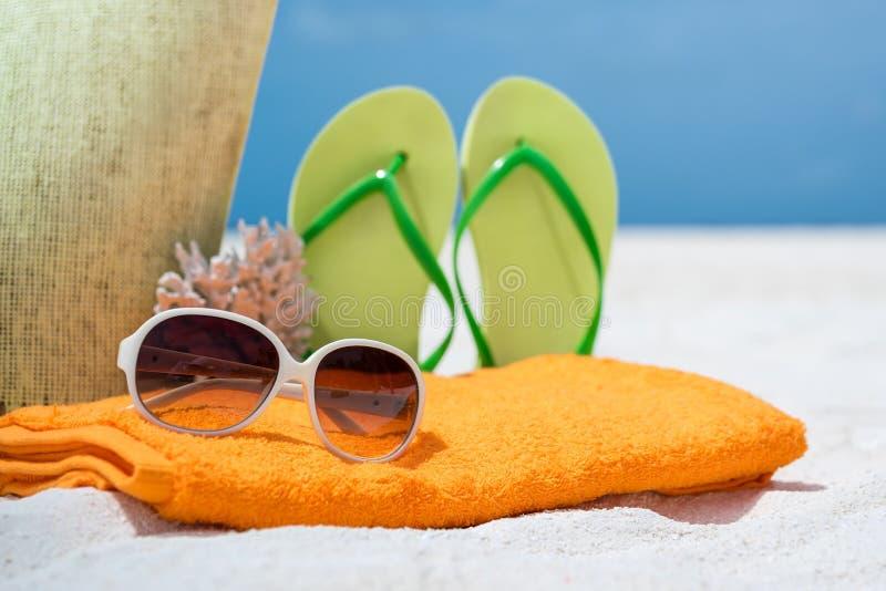 Sac de plage d'été avec le corail, la serviette, les lunettes de soleil et les bascules électroniques photos libres de droits