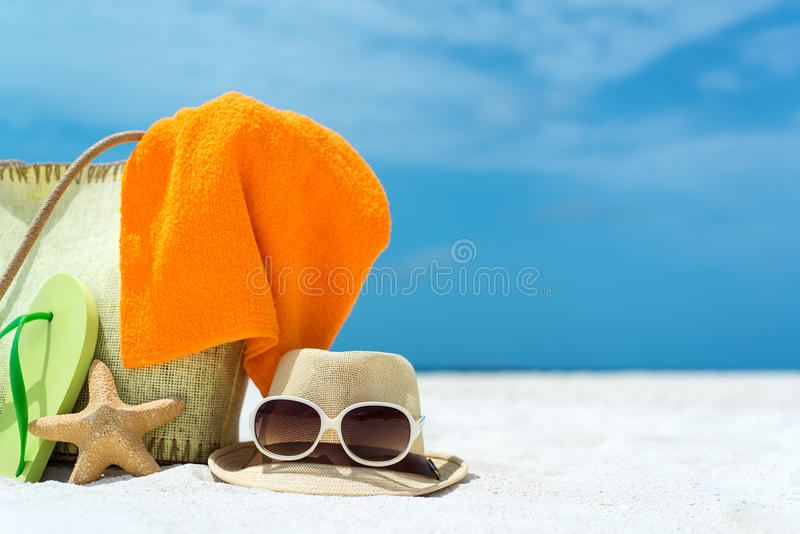 Sac de plage d'été avec les étoiles de mer, la serviette, les lunettes de soleil et les bascules électroniques sur la plage sablo images stock