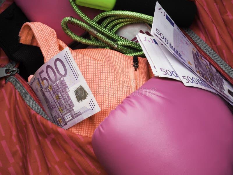 Sac de sports et équipement de gymnase comme gants de boxe, corde à sauter, molleton, et argent d'euro d'argent liquide photo libre de droits