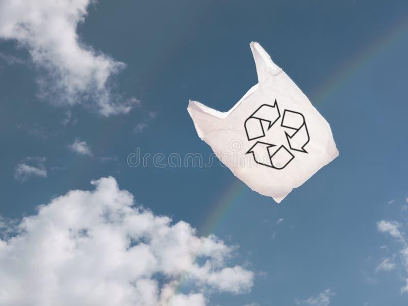 Sac de transporteur en plastique blanc au-dessus du ciel et de l'arc-en-ciel, soufflant dans le vent photographie stock