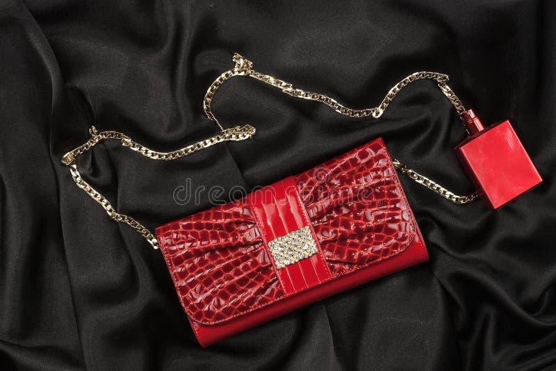Sac du parfum en cuir et rouge laqué se trouvant sur la soie noire Sac à main pour les femmes et la bouteille de parfum, vue supé photo libre de droits