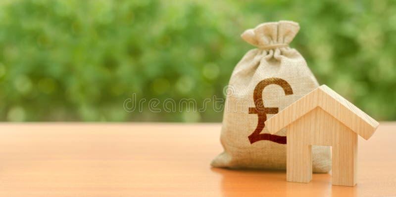 Sac en bois de figurine de maison et d'argent de livre sterling sur le fond de la nature Budget, fonds subventionnés Cl? de Chamb photographie stock libre de droits