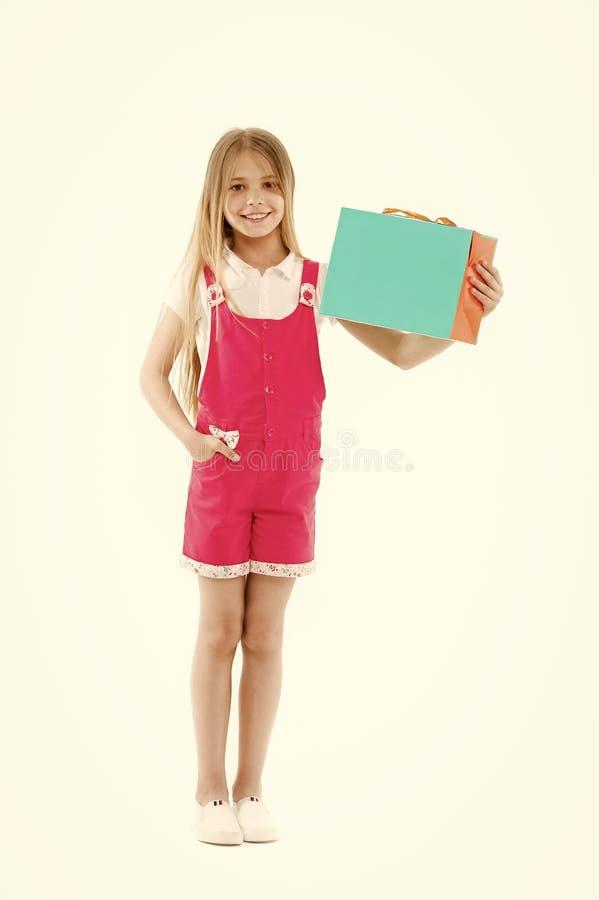 Sac en papier heureux de prise de fille d'isolement sur le blanc Peu sourire shopaholic avec le panier Client d'enfant souriant a image stock