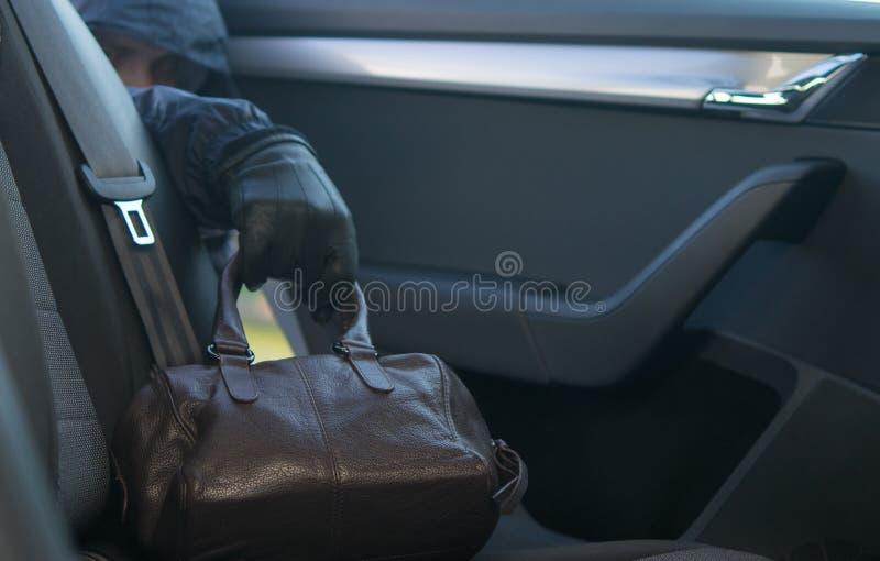 Sac oublié dans le siège arrière, volé à la main, gant noir photo stock