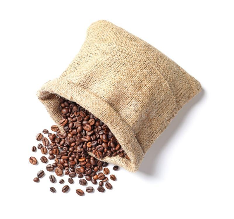 Sac retourné avec les grains de café rôtis sur le fond blanc photographie stock libre de droits