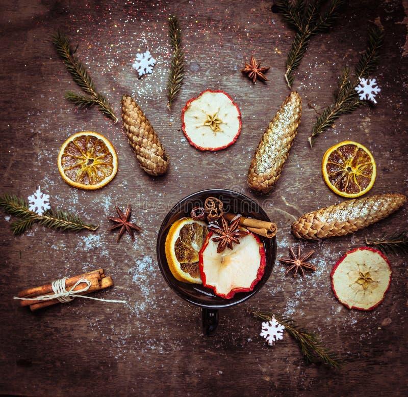 Sacador caliente del vino en taza oscura con las especias y las frutas del invierno en la tabla de madera foto de archivo libre de regalías