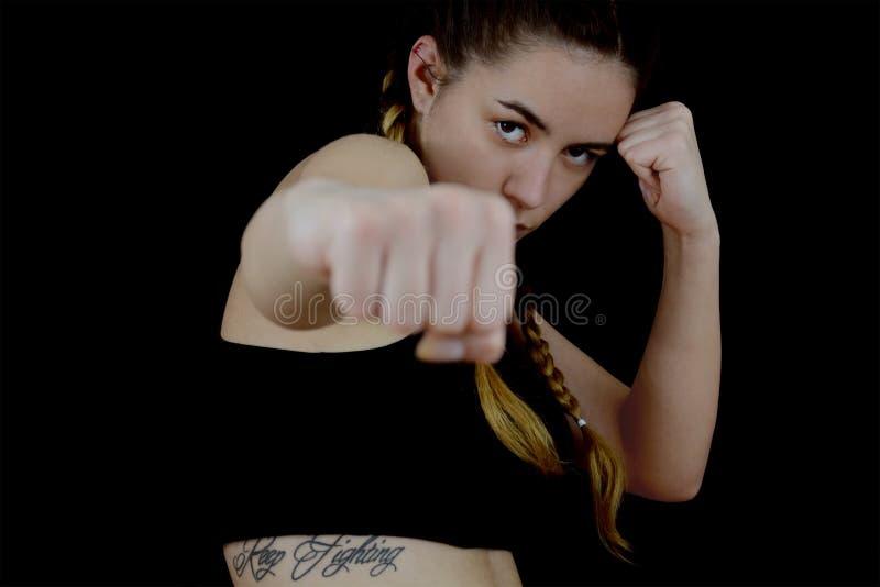 Sacador del boxeo del entrenamiento de la muchacha en fondo negro foto de archivo