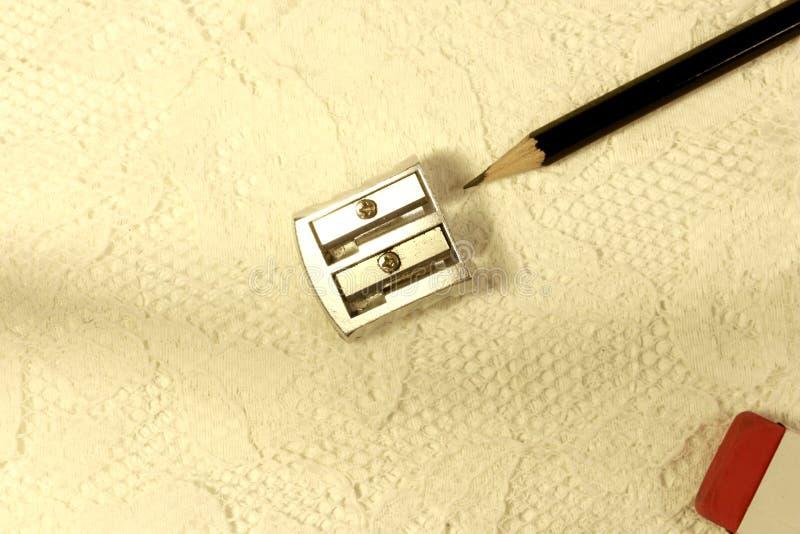 Sacapuntas de lápiz, lápiz del grafito y un borrador en la tela blanca del cordón foto de archivo