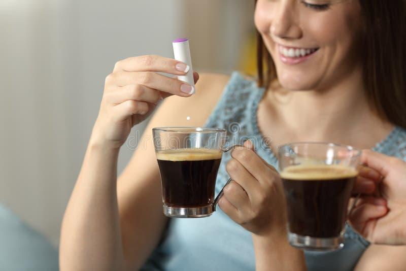 Sacarino que lanza de la mano de la mujer en una taza de café imagenes de archivo