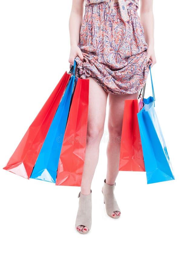 Sacchetti della spesa alla moda e rappresentazione della tenuta della giovane donna il suo le immagine stock