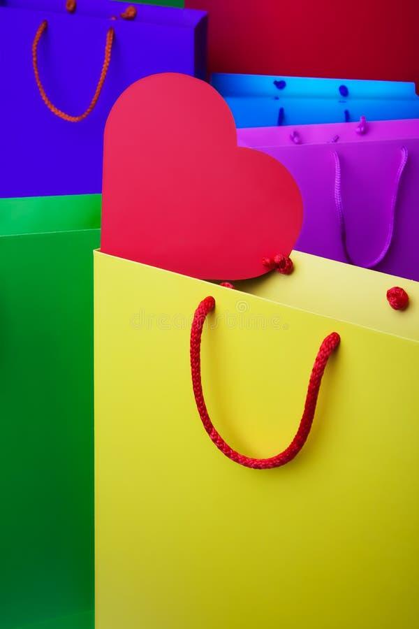 Sacchetti della spesa di carta Colourful con cuore rosso fotografia stock