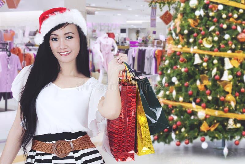 Sacchetti della spesa di trasporto della bella donna in centro commerciale fotografia stock