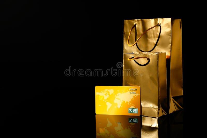 Sacchetti della spesa dorati con la carta di credito su fondo nero immagini stock