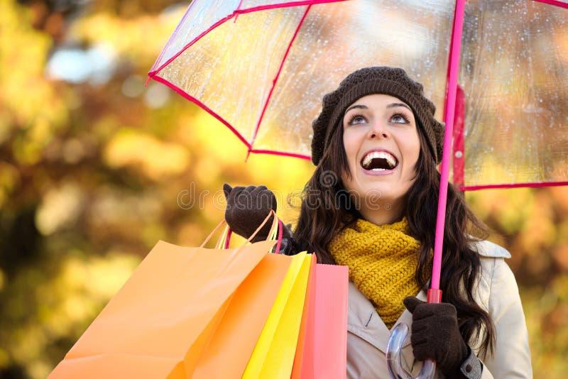 Sacchetti della spesa ed ombrello della tenuta della donna in autunno fotografia stock libera da diritti