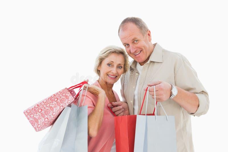 Sacchetti della spesa maturi sorridenti della tenuta delle coppie immagini stock libere da diritti