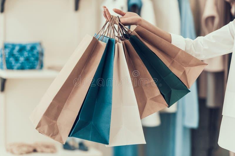 Sacchetti della spesa della tenuta della ragazza del primo piano in deposito fotografia stock libera da diritti
