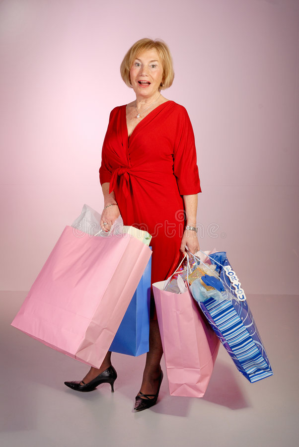 Sacchetti di acquisto attraenti della holding della signora più anziana fotografie stock