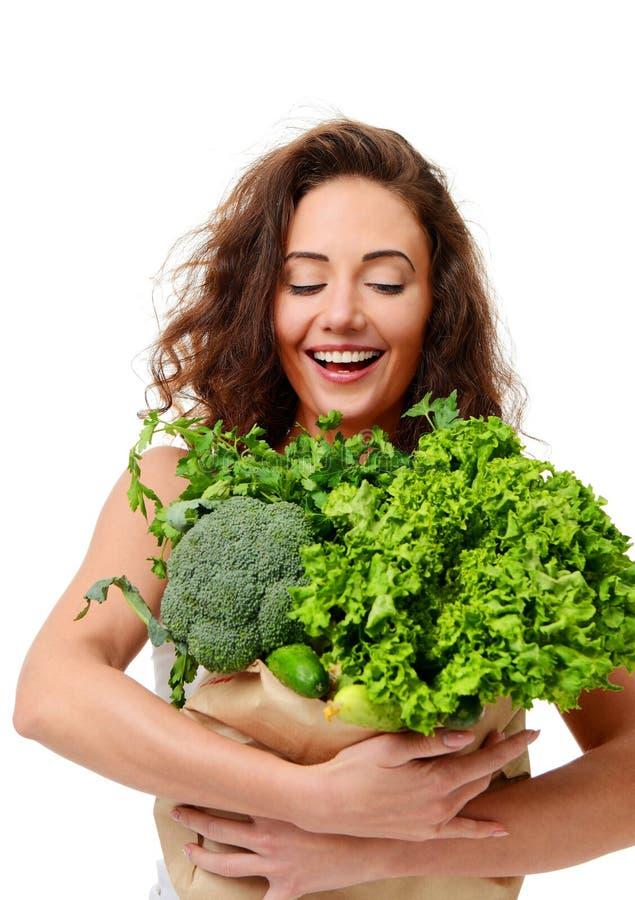 Sacchetto della spesa della carta della drogheria della tenuta della giovane donna in pieno delle verdure verdi fresche immagini stock libere da diritti