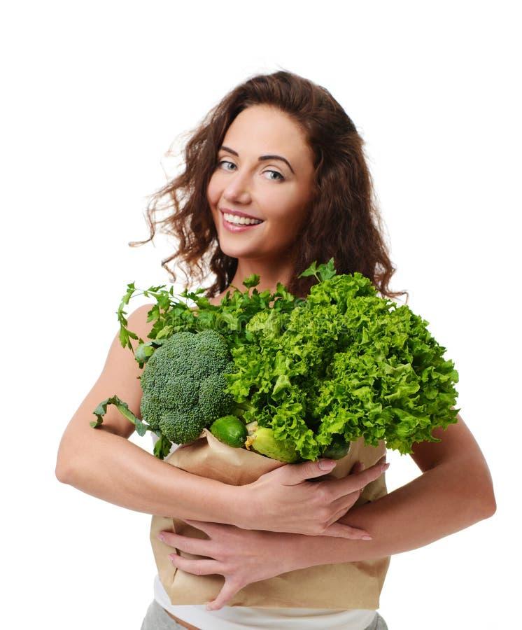 Sacchetto della spesa della carta della drogheria della tenuta della giovane donna in pieno delle verdure verdi fresche fotografia stock libera da diritti