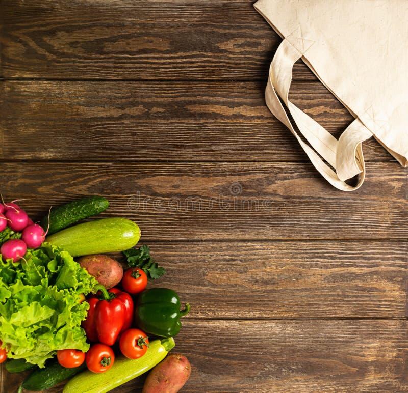 Sacchetto della spesa del cotone e verdure rustiche fresche su un fondo di legno Concetto di Eco Copi lo spazio Disposizione pian fotografia stock