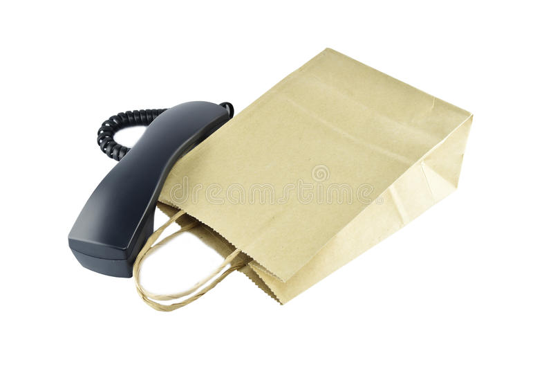 Sacchetto della spesa della carta di Brown con il telefono su fondo bianco fotografie stock libere da diritti