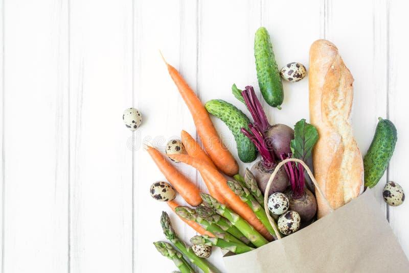 Sacchetto della spesa di carta con pane fresco e le verdure Disposizione piana, vista superiore fotografia stock