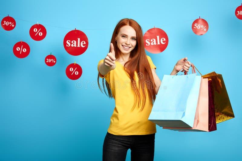 Sacchetto della spesa sorridente affascinante felice della tenuta della donna con i vestiti e di mostra il pollice su immagini stock