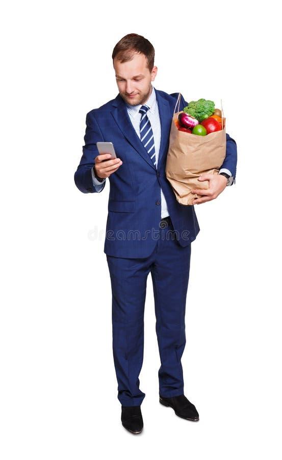 Sacchetto della spesa sorridente della tenuta dell'uomo d'affari in pieno delle verdure isolate su fondo bianco fotografie stock libere da diritti