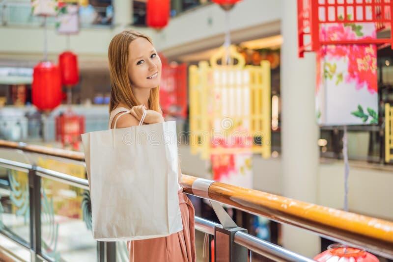 Sacchetto della spesa della tenuta della donna contro lo sfondo delle lanterne rosse cinesi per il nuovo anno cinese Grande vendi fotografia stock libera da diritti