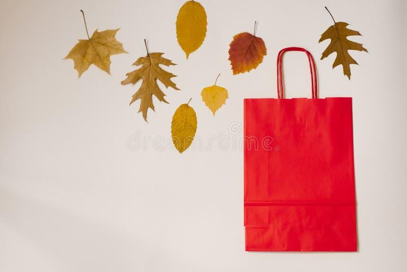Sacchetto di carta Kraft rosso con maniglie e foglie gialle cadute autunnali su fondo beige Copia spazio Sconto, promozioni, s immagini stock