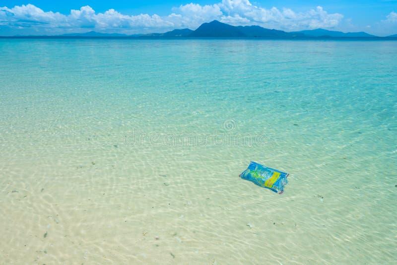 Sacchetto di plastica monouso disgarded nella riserva marina incontaminata fotografia stock
