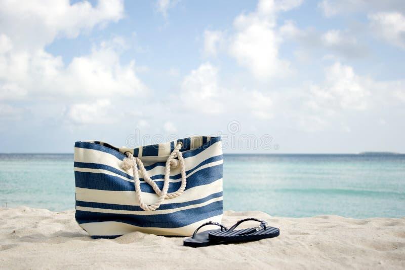 Sacchetto e flip-flop sulla spiaggia fotografie stock libere da diritti