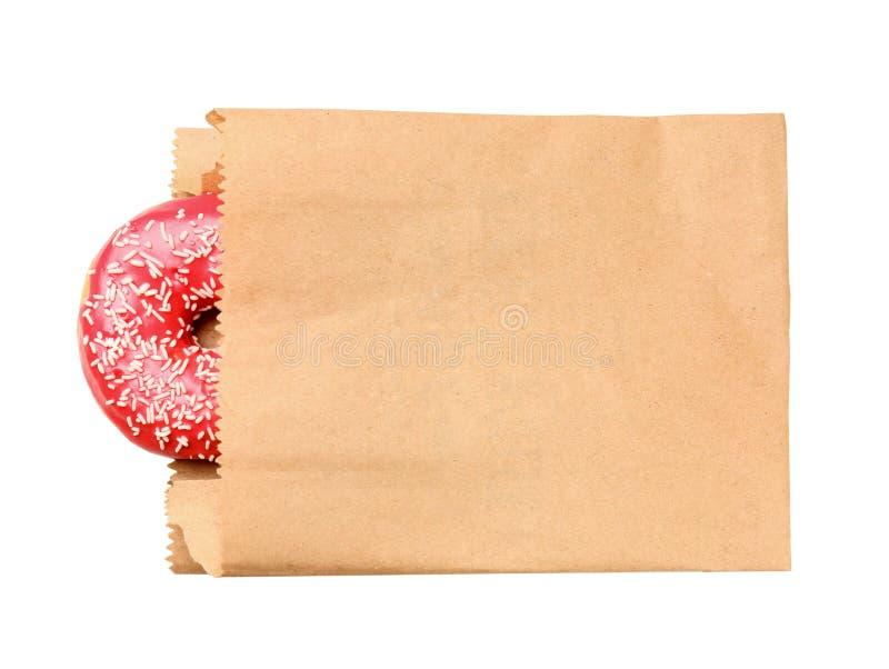 Sacco di carta con la ciambella su fondo bianco, vista superiore fotografia stock libera da diritti
