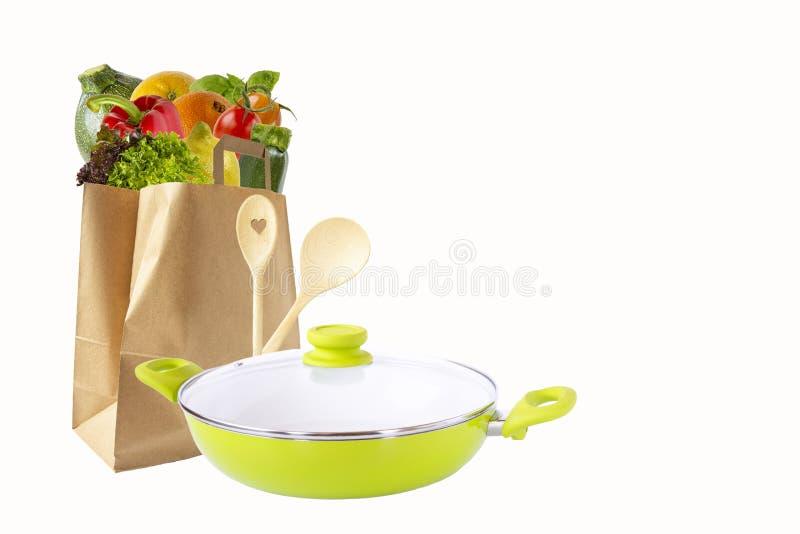 Sacco di carta con le verdure e frutta, padella verde e cucchiai di legno Acquisto dei prodotti Oggetti isolati su priorit? bassa fotografia stock