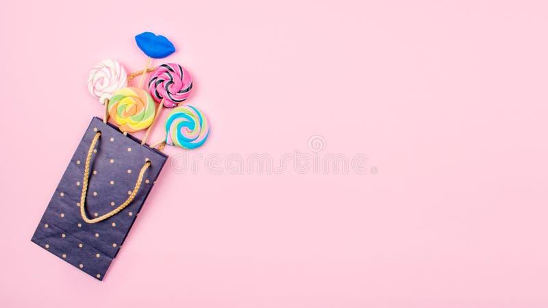 Sacco di carta con molte caramelle variopinte della lecca-lecca su fondo rosa pastello Fondo festivo minimo luminoso, cartolina d fotografie stock