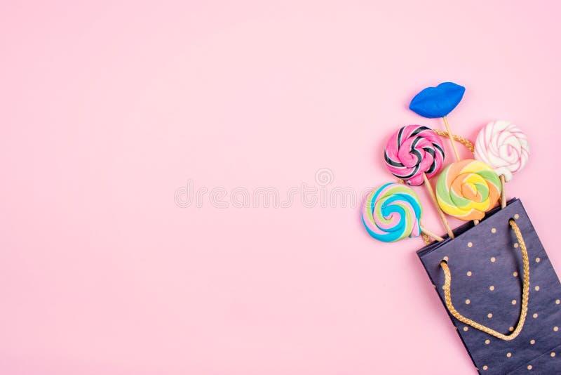 Sacco di carta con molte caramelle variopinte della lecca-lecca su fondo rosa pastello Fondo festivo minimo luminoso, cartolina d fotografia stock