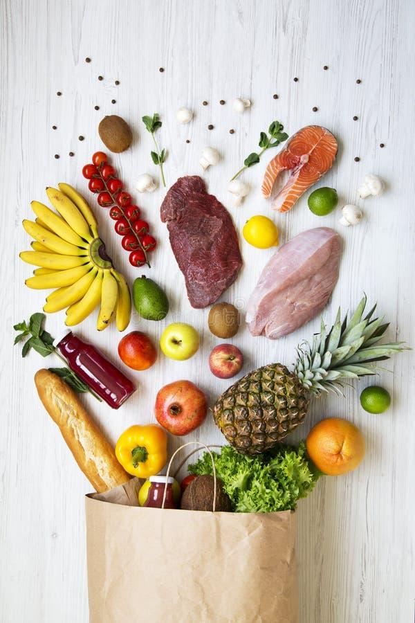 Sacco di carta della frutta e delle verdure differenti sulla tavola di legno bianca Fondo sano dell'alimento, vista superiore fotografia stock libera da diritti