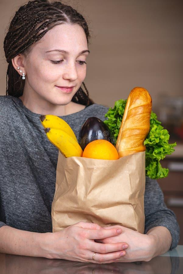 Sacco di carta pieno della tenuta della donna con i prodotti in mani sui precedenti della cucina Alimento biologico sano e fresco immagine stock libera da diritti