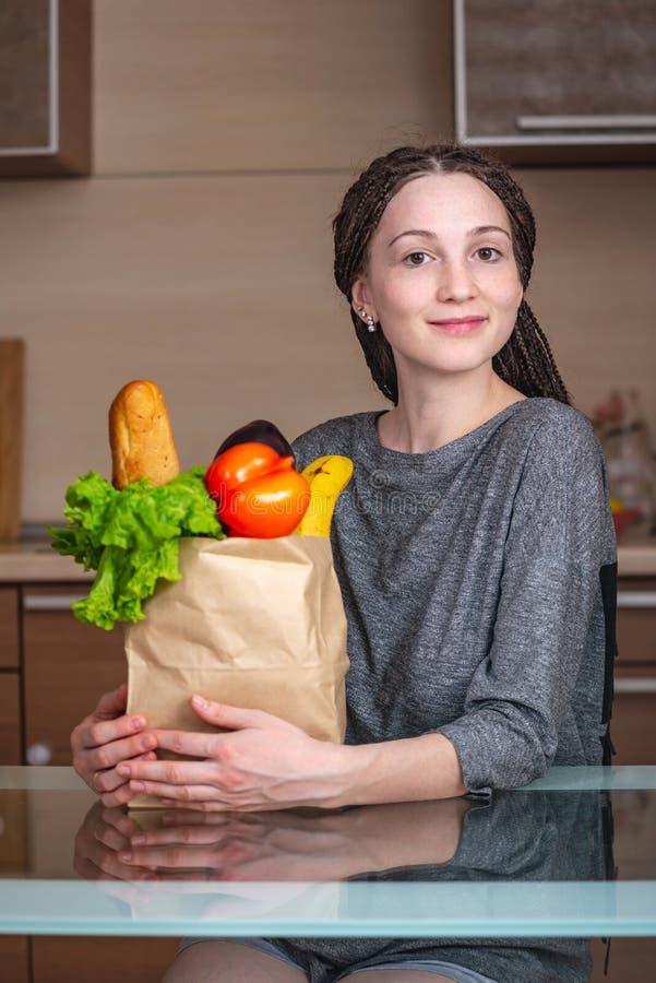 Sacco di carta pieno della tenuta della donna con i prodotti sui precedenti della cucina Alimento biologico fresco per una dieta  fotografia stock