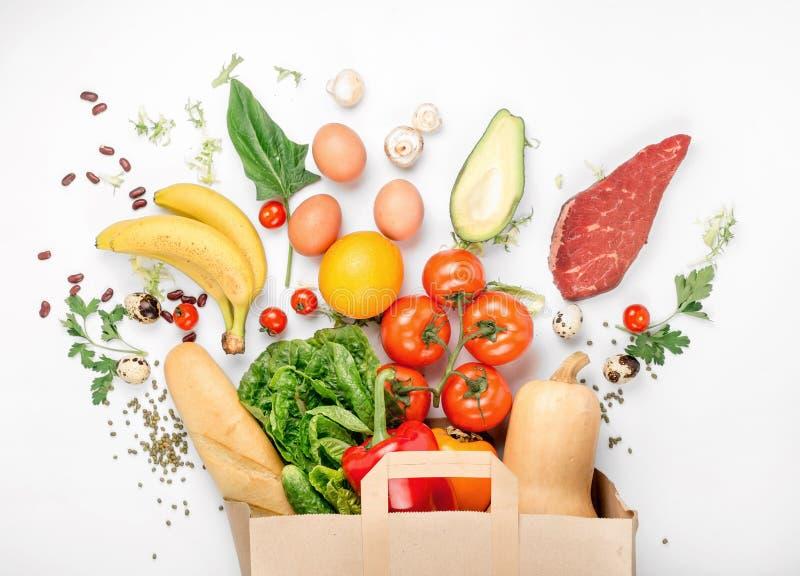 Sacco di carta pieno di alimento salutare differente su fondo bianco fotografia stock libera da diritti